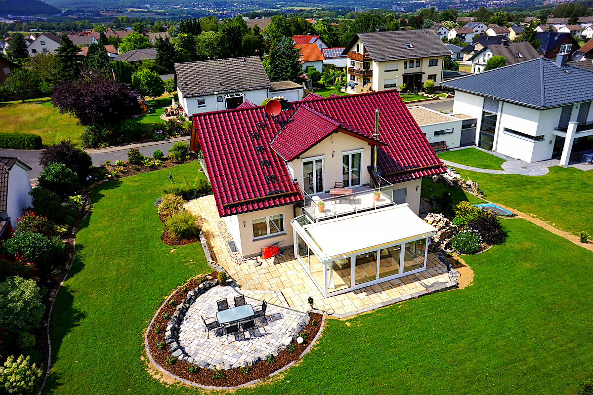 Moderne Immobilienfotografie: Luftaufnahme von ihrem Haus mit Kamera Drohne erstellt