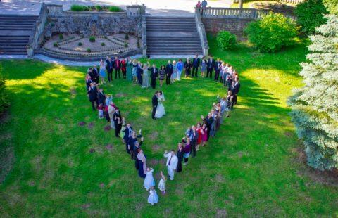 Fotografie einer Hochzeit per Drohne: Die Hochzeitsgesellschaft formt ein Herz mit dem Hochzeitspaar im Mittelpunkt (Foto: Mirko Baum).